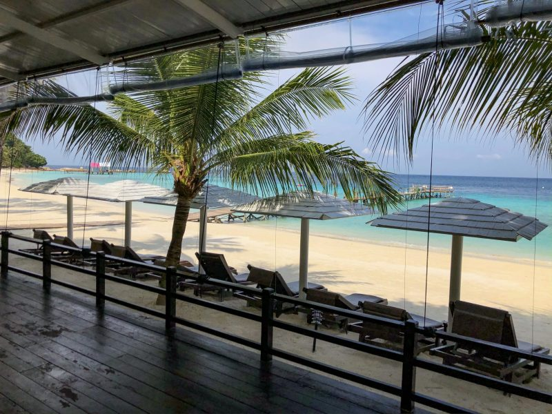 seaview cafe seating area with sun loungers overlooking white sandy beach and azure sea at summer bay lang tengah island