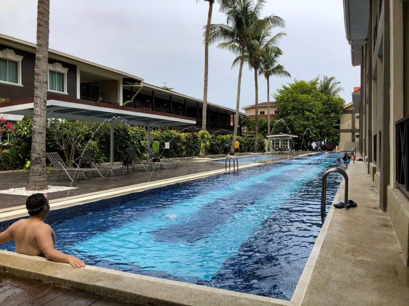 man swimming in olympic size pool at summer bay resort