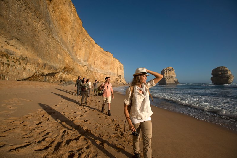 group of people trekking on the beach next to the 12 apostles in victoria