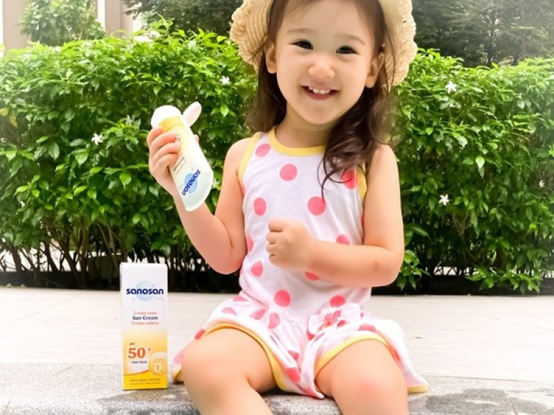 best baby sunscreen in malaysia, happy toddler holding sunscreen outdoors