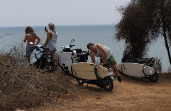 3 scooters with board racks, a board in each, and the boys checking the surf