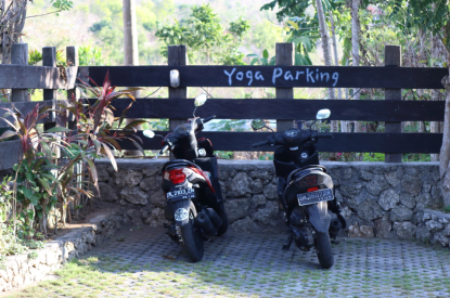 2 scooters parked in front of a sign saying yoga parking