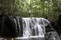 Dan standing on top of the waterfall arms outstretched, trees surrounding him