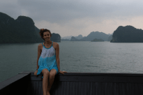 Tegan sitting on the back of the boat, grey skies, dark wood contrasting with the blue water and shadowed limestone mountains