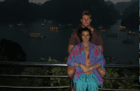 Couple shot, Dan sitting on the railing, Tegan standing between his legs, boats lit up in the bay