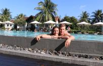 Dan and Tegan in the pool, Dan standing behind with his arms over Tegan