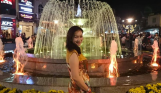 A beautiful vietnamese woman standing in front of a water fountain all light up at night