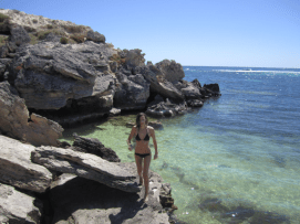 Tegan standing on a rocky ledge post swim, black bikini contrasting with the super clear blue/green water below
