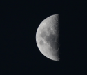 Half moon, black sky, white moon with visible craters