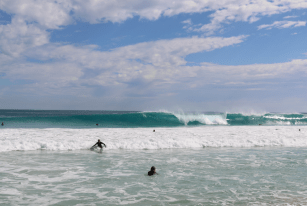 Solid right hander breaking out the back, surfers paddling out, a few clouds in the sky