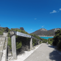 The sign to the picturesque beach, footpath, shubbery on either side and the turquoise ocean in the distance