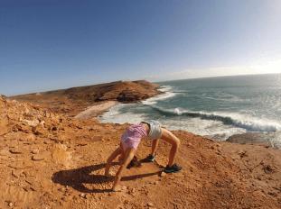 Tegan in wheel pose on top of the rocks/cliffs that make up the coastal walk in Kalbarri