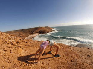 Tegan in wheel pose on top of the rocks/cliffs that make up the coastal walk in Kalbarri