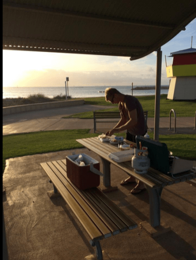 Dan cooking dinner on the picnic tables in Geraldton, sunsetting behind him