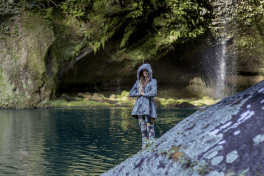 Tegan standing with hands in prayer background blurred, spray from the waterfall in the right hand corner