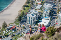 Girls sitting on the rocks on top of the Mount, buildings below