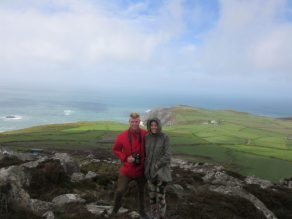 Tegan and Dan standing atop a lookout, vibrant green fields and blue ocean behind them