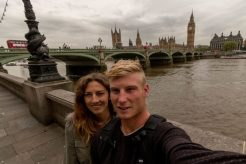 Couple selife in front of the London bridge, river thames behind us and grey skies