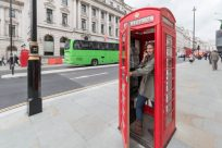 Tegan standing in a red telephone box pretending to talk on the phone with the door open