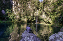Tegan and Dan sitting on a rock looking at the waterfall