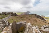 World War 1 lookout atop a cliff, broken rocks but a nice view of green fields and ocean, grey skies above with patches of blue.