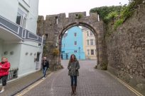 Tegan standing under an archway in Tenby. Blue faced building next to a yellow faced building in the background.