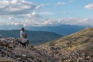 Tegan sitting on a rock overlooking the city below