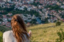 Tegan sitting on the rock at the top of the hill overlooking the city