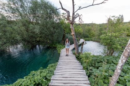 Tegan standing on a wooden path with a blue green clear lake on either side