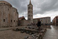 Tegan standing on some rocks in front of a pebbled building in the old town