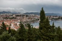 View over split, half ocean, half buildings, moutains in the distance