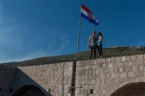 Tegan and dan standing under the croatian flag on the wall