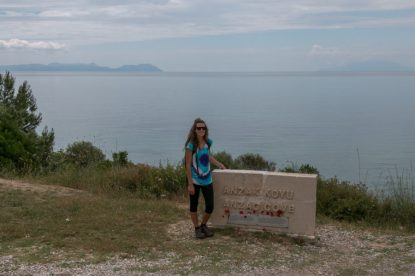 Tegan standing next to the white brick fence saying Anzac cove with the sea behind her