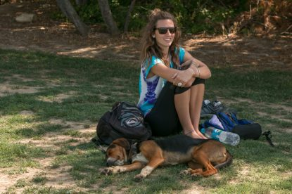 A sleepy dog right next to Tegan sitting on the grass