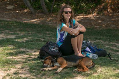 A sleepy dog right next to Tegan sitting on the grass