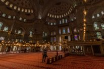 Windows, lights and tiles inside the blue mosque, red carpet
