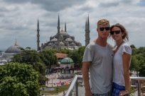 Tegan and Daniel standing on the balcony of a rooftop restaurant, blue mosque in the backround looking like a fake backdrop!