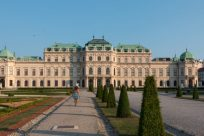 Tegan walking towards Belvedere Palace, trimmed hedges t the right, flowers to the elft