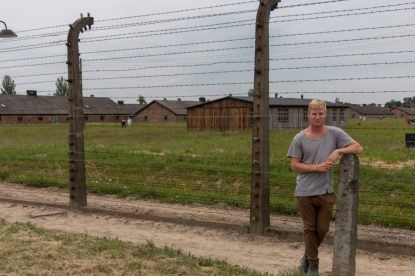 Dan standing infront of the 5m high fences, barracks in the background