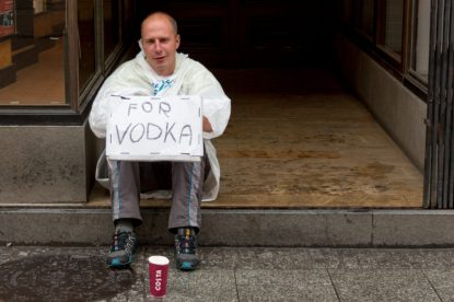 Bald man sitting on the curb with a red cup and a sign saying 'For Vodka'