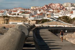 Concrete pier with white houses with orange roofs on the hill