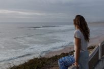 Tegan sitting on the fence watching the surf