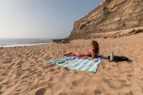 Tegan laying on the turkish towel on the beach