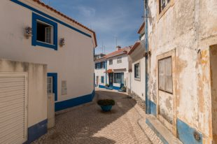 Blue and white buildings with white cobblestone roads