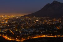 City lights at night, table mountain a dark silhouette