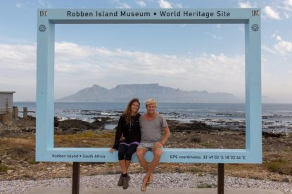 us sitting on the sign framing table mountain from Robben Island