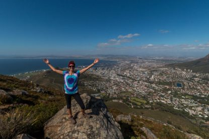 Tegan arms outstretched on top of Lions rock, tiny tiny houses in the distance