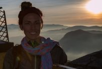 Tegan standing happy atop Adams Peak, mist rolling in over the mountains