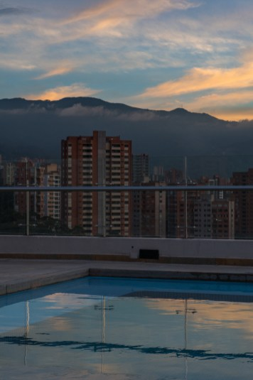 Sunset sky reflecting in the rooftop swimming pool