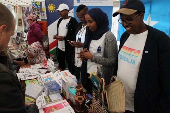 Kuvassa Seuran vapaaehtoiset esittelevät toimintaa Maailma kylässä- festivaalilla, esitteitä ja tuotteita pöydällä